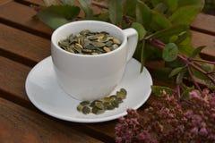 Um copo de sementes de abóbora foto de stock