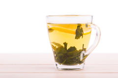 Um copo de vidro completo do chá verde Um copo em uma tabela de madeira clara Um copo bonito com limão e as folhas de chá verdes  fotos de stock