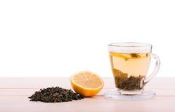 Um copo de vidro completo do chá verde Um copo em uma tabela de madeira clara Um copo bonito com o limão e as folhas de chá verde fotos de stock