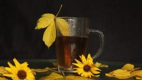 Um copo de vidro transparente está molhado na chuva do chá quente no meio de uma paisagem do outono: folhas caídas amareladas, fl filme