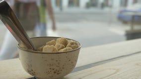 Um copo do açúcar mascavado está na tabela no café, oposto à grande janela vídeos de arquivo