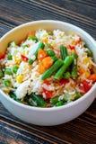 Um copo do arroz branco com vegetais em um fundo de madeira escuro Preparado sem perda de vitaminas fotografia de stock