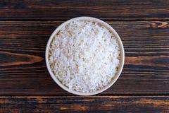 Um copo do arroz branco em um fundo de madeira escuro Alimento dietético ou do vegetariano Vista superior Alimento cozinhado em c fotografia de stock royalty free
