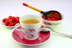 Um copo do atolamento do chá e de framboesa fotos de stock