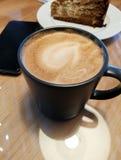 Um copo do café do cappuccino em uma tabela em um café ao lado de você pode ver uma placa com um bolo marrom imagens de stock