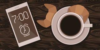 Um copo do café da manhã com croissant e um telefone celular em uma tabela de madeira Fotografia de Stock Royalty Free