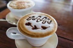 Um copo do café do cappuccino com arte do latte da coração-forma Fotografia de Stock Royalty Free