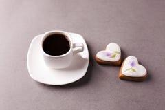 Um copo do café e um grupo de cookies com aysing na forma de um coração em um fundo cinzento, concisão, minimalismo foto de stock royalty free
