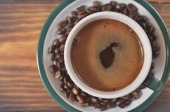 Um copo do café forte com uma espuma em uns pires com feijões de café em um fundo de madeira Fotos de Stock