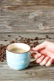 Um copo do café perfumado em uma mão do ` s da mulher contra um fundo de feijões e de madeira de café foto de stock royalty free