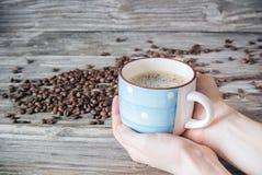 Um copo do café perfumado nas mãos do ` um s da mulher contra um fundo de feijões e de madeira de café imagem de stock royalty free