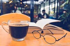 Um copo do café preto com vidros de leitura na tabela e abre a vaia Fotos de Stock Royalty Free