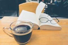 Um copo do café preto com vidros de leitura na tabela e abre a vaia Imagens de Stock Royalty Free