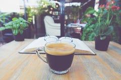 Um copo do café preto com vidros no livro na tabela no jardim Fotos de Stock