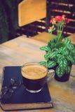 Um copo do café preto com vidros no livro na tabela no jardim Fotos de Stock Royalty Free