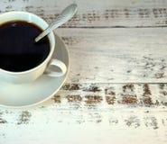 Um copo do café preto em uns pires com uma colher em uma tabela de madeira foto de stock royalty free