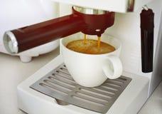 Um copo do café do café que está sendo feito pela máquina fotografia de stock