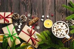 Um copo do café quente com marshmallow, ramos spruce, cones, presentes do Natal, canecas de laranja, flocos de neve, canela, nova fotografia de stock