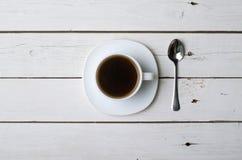 Um copo do café quente em uma tabela de madeira branca, vista superior Fotografia de Stock Royalty Free