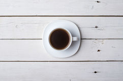 Um copo do café quente em uma tabela de madeira branca, vista superior Foto de Stock