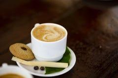 Um copo do café quente na placa branca com bolo, paz do bastão e folhas Colocado no contador velho da barra Cuba, espaço para o t fotografia de stock royalty free