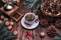 Um copo do café quente perfumado cercado pela parafernália festiva Moedor de café velho, cesta com cones e nozes foto de stock royalty free