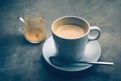 um copo do cappuccino na obscuridade rústica - do cimento da placa vida azul ainda Foto de Stock