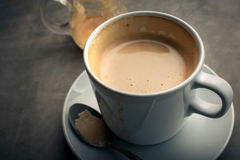 um copo do cappuccino na obscuridade rústica - do cimento da placa vida azul ainda Foto de Stock Royalty Free