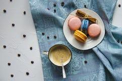 Um copo do cappuccino quente com canela e os bolinhos de am?ndoa multi-coloridos do bolo imagens de stock royalty free