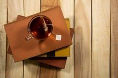 Um copo do chá é ficado situado no livro E grupo em uma composição de tabela de madeira com o espaço da cópia no fundo de madeira imagem de stock royalty free