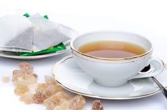Um copo do chá com açúcar e saquinhos de chá Imagem de Stock Royalty Free