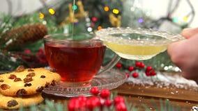 Um copo do chá com mel e cookies, um ramo de uma árvore de Natal na neve, luzes de Natal filme