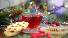 Um copo do chá com mel e cookies, um ramo de uma árvore de Natal na neve, luzes de Natal vídeos de arquivo