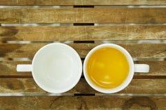 Um copo do chá & copo vazio na tabela de madeira Foto de Stock Royalty Free
