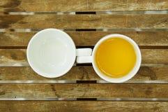 Um copo do chá & copo vazio na tabela de madeira Fotos de Stock Royalty Free