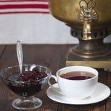 Um copo do chá, de um doce de cereja e de um samovar Imagem de Stock