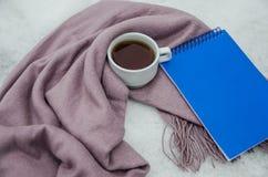 Um copo do chá delicioso é envolvido em um lenço morno, um caderno azul imagens de stock royalty free
