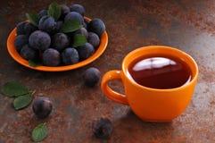 Um copo do chá e da ameixa na tabela fotografia de stock