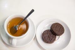 Um copo do chá e das cookies na tabela no fundo branco fotografia de stock
