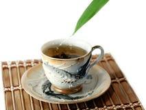 Um copo do chá e das gotas isolados no branco Imagem de Stock Royalty Free
