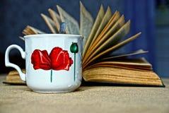 Um copo do chá e de um livro aberto fotos de stock