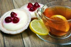 Um copo do chá e dos bolos imagens de stock