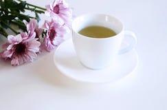 Um copo do chá e o crisântemo cor-de-rosa florescem na tabela Fundo borrado imagem de stock royalty free