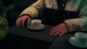 Um copo do chá e uma mão do ` s do homem em um café vídeos de arquivo