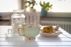 Um copo do chá ou do café quente com um bolo na tabela Imagens de Stock