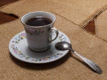 Um copo do chá preto em uns pires está na tabela com guardanapo fotografia de stock