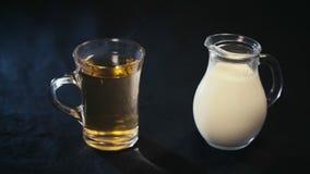 Um copo do chá verde e um jarro de leite vídeos de arquivo