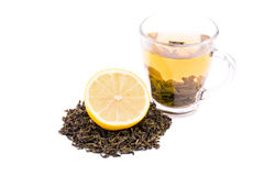 Um copo do chá verde isolado em um fundo branco Um copo de chá doce ao lado de um limão do corte e um montão do chá verde natural imagens de stock royalty free