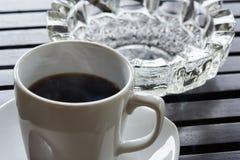 Um copo do cinzeiro quente do café e do cigarro na tabela foto de stock