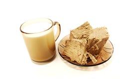 Um copo do leite e do halva Fotografia de Stock Royalty Free